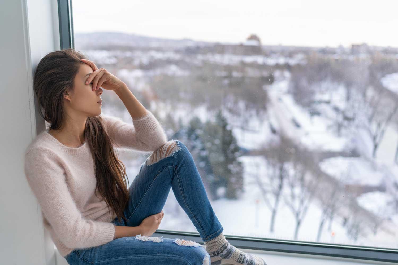 Frau-sitzt-auf-Fensterbank-deprimiert-Winterdepression