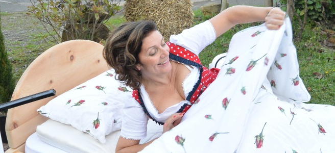 Frau-im-Dirndl-ist-freudig-über-die-Decke-und-den-Polster-von-Nikken-in-Ihrem-Bett